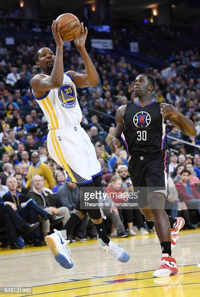 Kevin Durant of the Golden State Warriors drives towards the basket and gets fouled by Brandon Bass of the LA Clippers during an NBA basketball game...