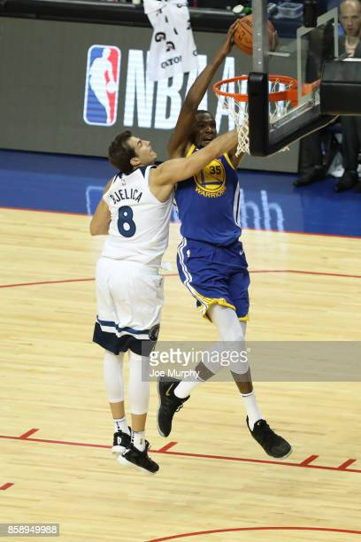 Kevin Durant of the Golden State Warriors dunks against Nemanja Bjelica of the Minnesota Timberwolves as part of the 2017 Global Games China on...