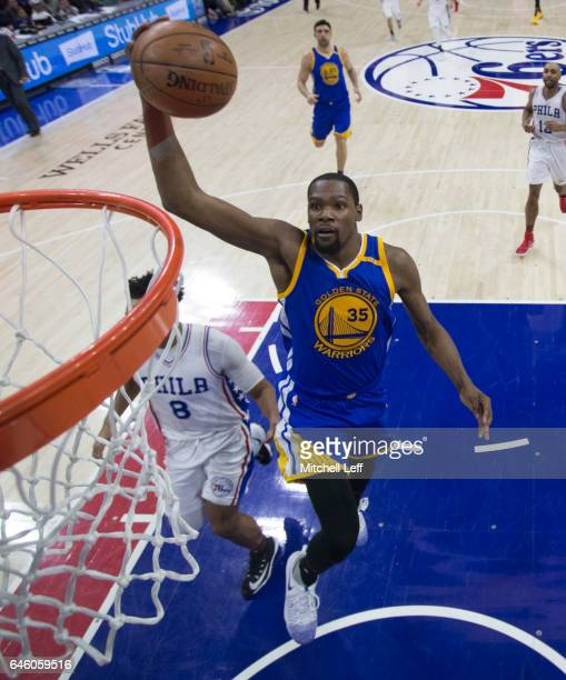 Kevin Durant of the Golden State Warriors dunks the ball past Jahlil Okafor of the Philadelphia 76ers in the third quarter at the Wells Fargo Center...
