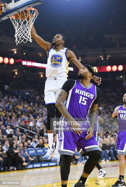 Kevin Durant of the Golden State Warriors goes up for a slam dunk over DeMarcus Cousins of the Sacramento Kings during an NBA Basketball game at...