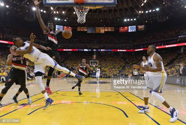 Kevin Durant of the Golden State Warriors goes up to pass the ball to Andre Iguodala and gets fouled by AlFarouq Aminu of the Portland Trail Blazers...