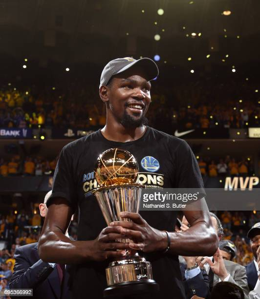 Kevin Durant of the Golden State Warriors holds up the Bill Russell Finals MVP Trophy after winning the Finals MVP after Game Five of the 2017 NBA...