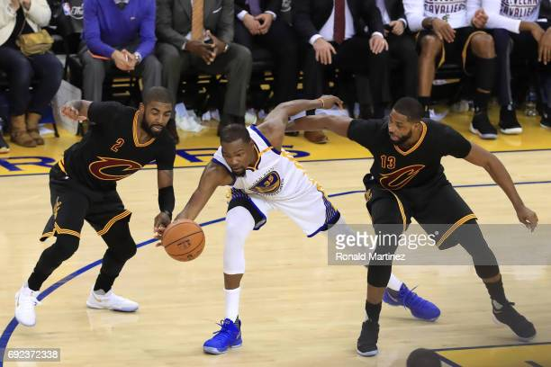 Kevin Durant of the Golden State Warriors is defended by Kyrie Irving and Tristan Thompson of the Cleveland Cavaliers during the second half of Game...