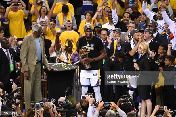 Kevin Durant of the Golden State Warriors is presented with the NBA Finals Most Valuable Player Trophy by NBA Hall of Famer Bill Russell after...