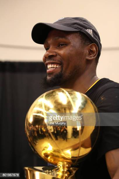 Kevin Durant of the Golden State Warriors poses for a photo with the Larry O'Brien Trophy and the Bill Russell Finals MVP Trophy during the postgame...