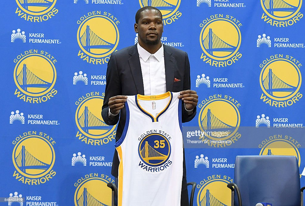 Kevin Durant of the Golden State Warriors poses with his new jersey during the press conference where he was introduced as a member of the Golden...
