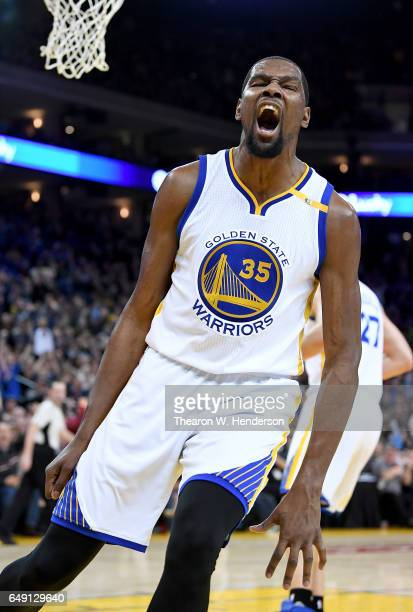 Kevin Durant of the Golden State Warriors reacts after slam dunking the ball against the LA Clippers during an NBA basketball game at ORACLE Arena on...