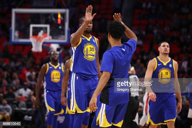 Kevin Durant of the Golden State Warriors reacts to two three made free throws in the fourth quarter with Quinn Cook while playing the Detroit...