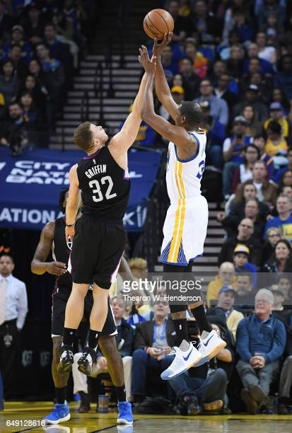 Kevin Durant of the Golden State Warriors shoots over Blake Griffin of the LA Clippers during an NBA basketball game at ORACLE Arena on February 23...