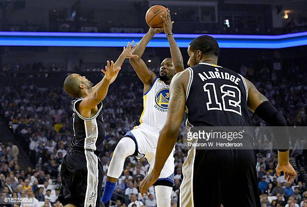 Kevin Durant of the Golden State Warriors shoots over Tony Parker of the San Antonio Spurs during the first quarter in an NBA basketball game at...