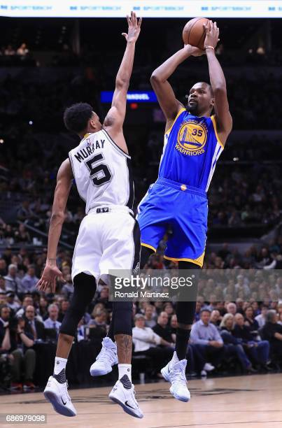 Kevin Durant of the Golden State Warriors shoots the ball against Dejounte Murray of the San Antonio Spurs in the first half during Game Four of the...