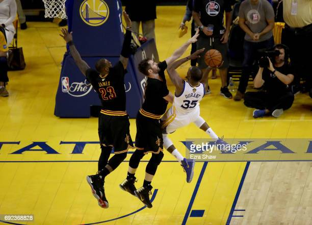 Kevin Durant of the Golden State Warriors shoots the ball against Kevin Love and LeBron James of the Cleveland Cavaliers in Game 2 of the 2017 NBA...