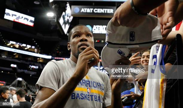 Kevin Durant of the Golden State Warriors signs autographs before the start of his team's game against the San Antonio Spurs at ATT Center on March...