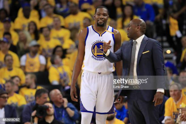 Kevin Durant of the Golden State Warriors speaks with acting head coach Mike Brown during Game Two of the NBA Western Conference Finals against the...