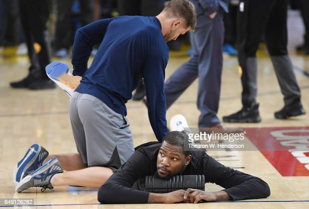 Kevin Durant of the Golden State Warriors stretches during warm ups prior to the start of an NBA basketball game against the LA Clippers at ORACLE...