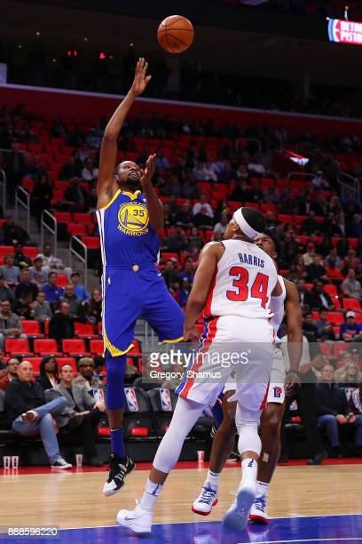 Kevin Durant of the Golden State Warriors takes a shot over Tobias Harris of the Detroit Pistons during the first half at Little Caesars Arena on...