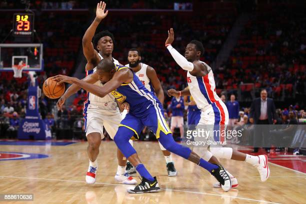 Kevin Durant of the Golden State Warriors tries to get around the defense of Reggie Jackson and Stanley Johnson of the Detroit Pistons during the...