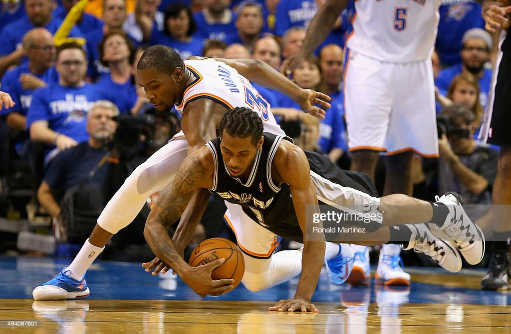 Kevin Durant #35 of the Oklahoma City Thunder and Kawhi Leonard #2 of the San Antonio Spurs go for a loose ball in the third quarter during Game Four of the Western Conference Finals of the 2014 NBA Playoffs at Chesapeake Energy Arena on May 27, 2014 in Oklahoma City, Oklahoma.