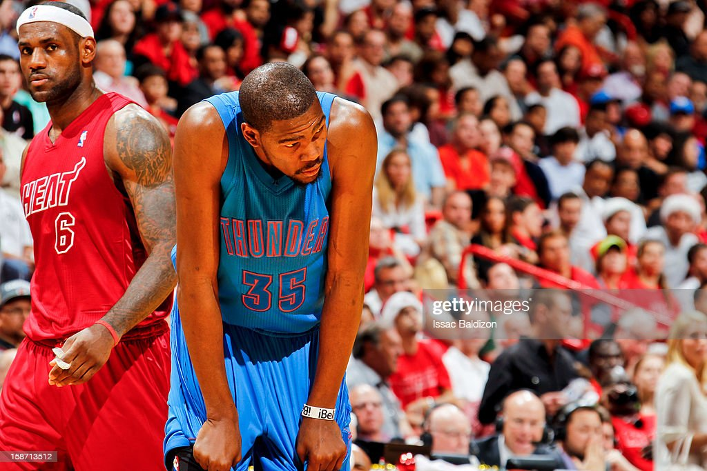 Kevin Durant #35 of the Oklahoma City Thunder and LeBron James #6 of the Miami Heat wait to resume action during a Christmas Day game on December 25, 2012 at American Airlines Arena in Miami, Florida.