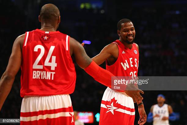 Kevin Durant of the Oklahoma City Thunder and the Western Conference reacts with teammate Kobe Bryant of the Los Angeles Lakers during the NBA...