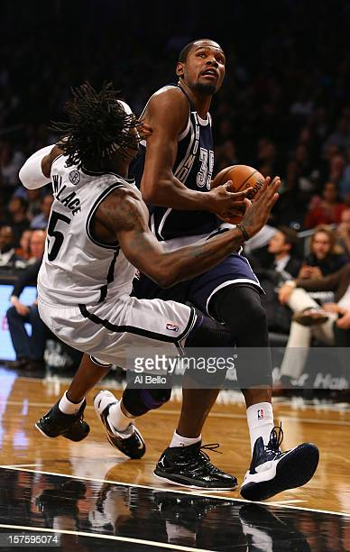 Kevin Durant of the Oklahoma City Thunder drives past Gerald Wallace of the Brooklyn Nets during their game at the Barclays Center on December 4 2012...