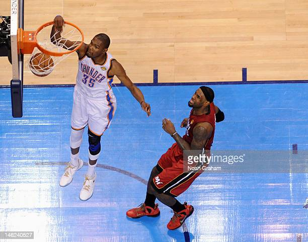 Kevin Durant of the Oklahoma City Thunder dunks the ball as LeBron James of the Miami Heat watches during Game One of the 2012 NBA Finals at...