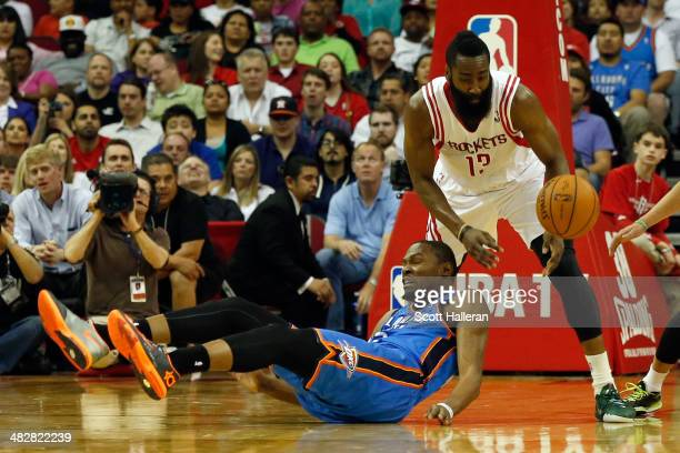 Kevin Durant of the Oklahoma City Thunder falls to the court after fighting for a ball against James Harden of the Houston Rockets in the second...