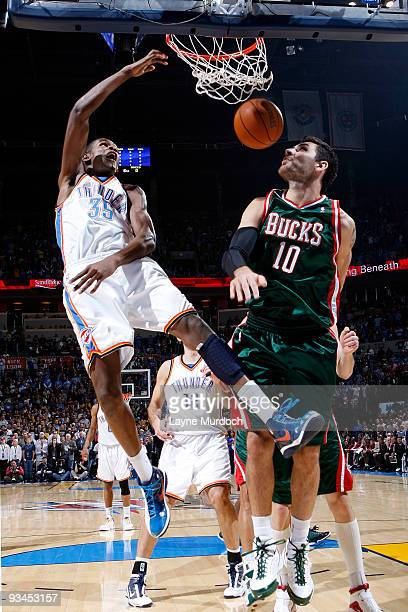Kevin Durant of the Oklahoma City Thunder finishes a dunk on Carlos Delfino of the Milwaukee Bucks on November 27 2009 at the Ford Center in Oklahoma...