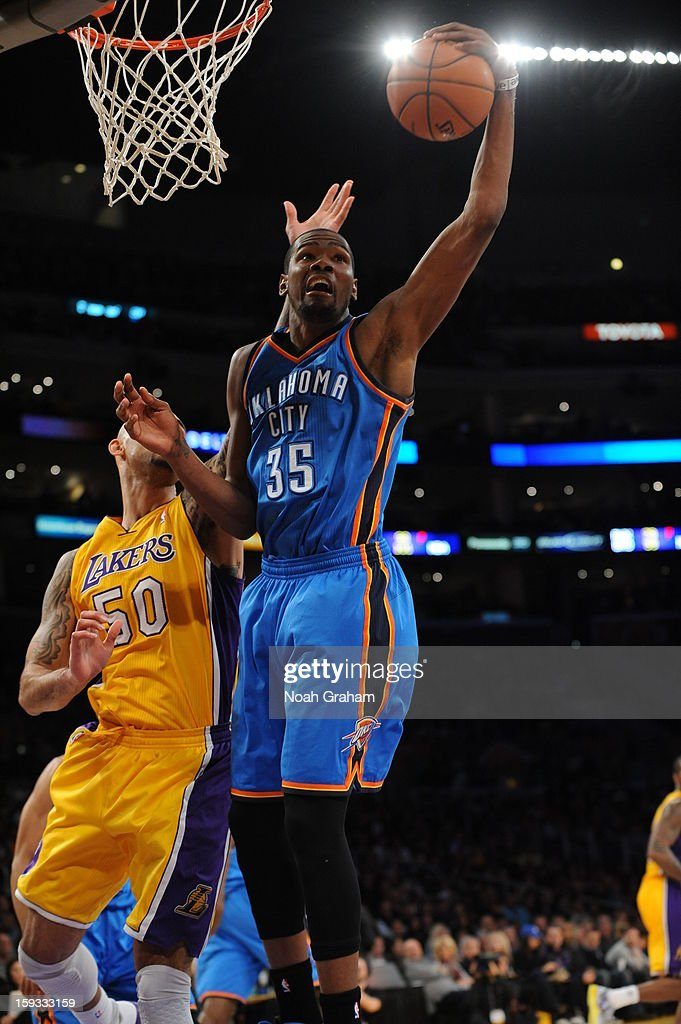 Kevin Durant #35 of the Oklahoma City Thunder goes up for a shot against Robert Sacre #50 of the Los Angeles Lakers at Staples Center on January 11, 2013 in Los Angeles, California.