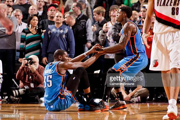 Kevin Durant of the Oklahoma City Thunder is helped up by teammate DeAndre Liggins while playing the Portland Trail Blazers on January 13 2013 at the...