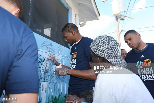 Kevin Durant of the Oklahoma City Thunder paints a mural during the NBA Cares AllStar Day of Service 'LIVE' with Rebuilding Together as part of the...