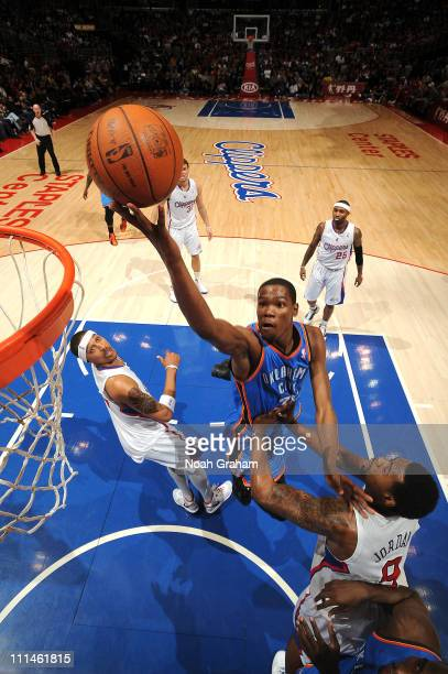 Kevin Durant of the Oklahoma City Thunder rises for a shot against Jamario Moon and DeAndre Jordan of the Los Angeles Clippers at Staples Center on...