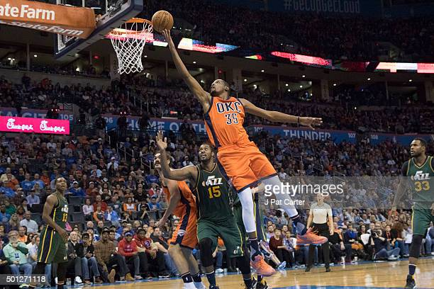 Kevin Durant of the Oklahoma City Thunder sails past Derrick Favors of the Utah Jazz for two points during the third period of a NBA game at the...