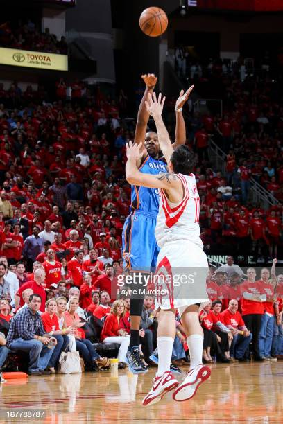 Kevin Durant of the Oklahoma City Thunder shoots a threepointer against Carlos Delfino of the Houston Rockets in Game Four of the Western Conference...