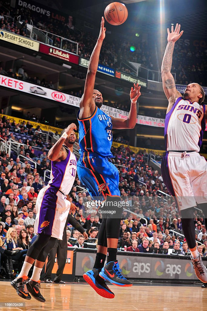 Kevin Durant #35 of the Oklahoma City Thunder shoots against Michael Beasley #0 of the Phoenix Suns on January 14, 2013 at U.S. Airways Center in Phoenix, Arizona.
