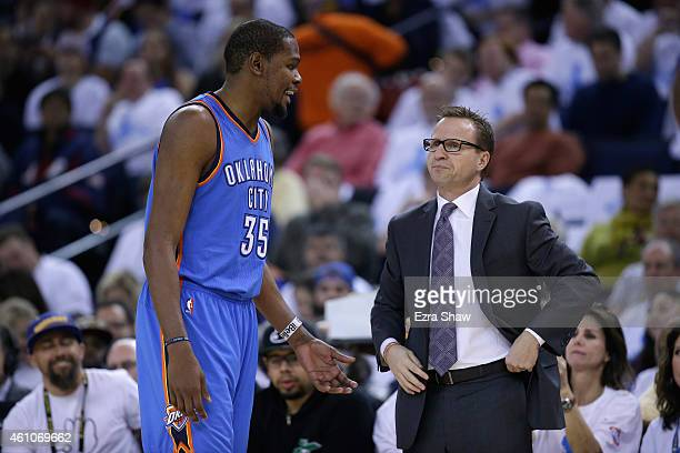 Kevin Durant of the Oklahoma City Thunder talks to head coach Scott Brooks of the Oklahoma City Thunder during their game against the Golden State...