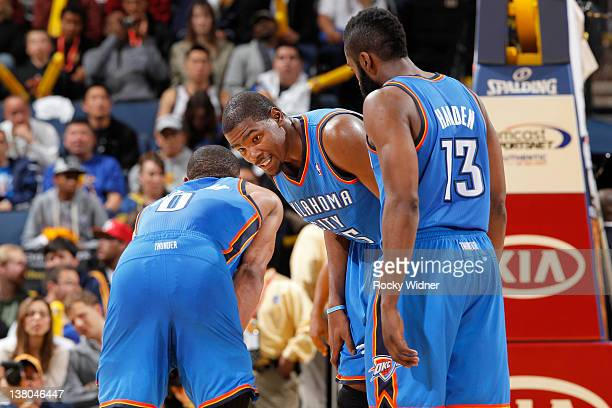 Kevin Durant of the Oklahoma City Thunder talks to teammates Russell Westbrook and James Harden of the Oklahoma City Thunder during a game against...