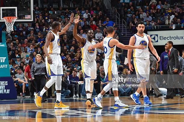 Kevin Durant Stephen Curry Draymond Green and Zaza Pachulia of the Golden State Warriors give each other high fives after a play against the...