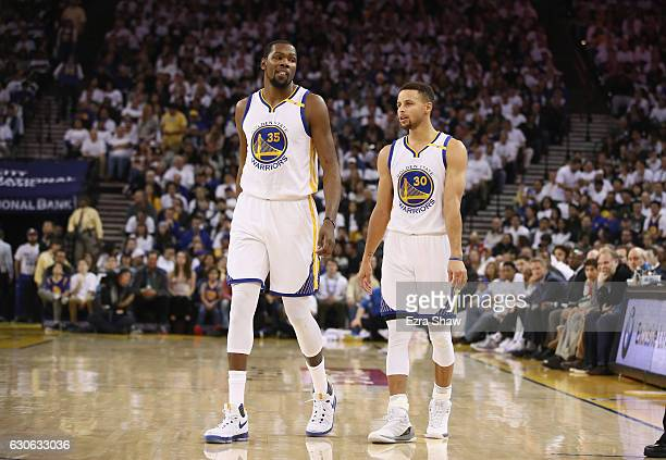 Kevin Durant talks to Stephen Curry of the Golden State Warriors during their game against the Toronto Raptors at ORACLE Arena on December 28 2016 in...