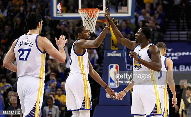 Kevin Durant Zaza Pachulia and Draymond Green of the Golden State Warriors high five during their game against the Detroit Pistons at ORACLE Arena on...