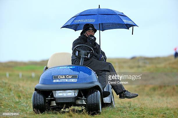 Kevin Feeney the European Tour referee sheltering from the rain on the second hole during the third round of the 2014 Alfred Dunhill Links...