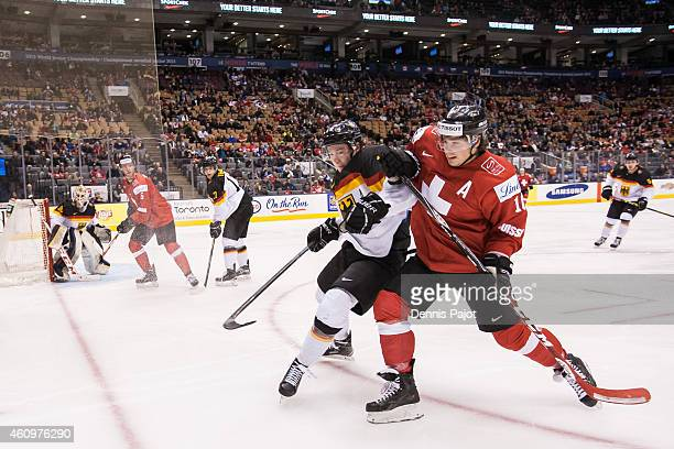 Kevin Fiala of Switzerland battles for the puck against Janik Moser of Germany during the 2015 IIHF World Junior Championship on January 02 2015 at...
