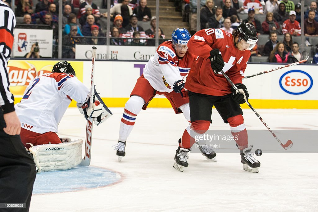 Kevin Fiala #10 of Switzerland battles out front of the net against David Nemecek #8 and Vitek Vanecek #2 of Czech Republic during the 2015 IIHF World Junior Championship on December 27, 2014 at the Air Canada Centre in Toronto, Ontario, Canada.