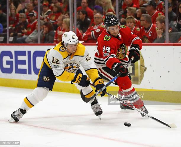 Kevin Fiala of the Nashville Predators and Jan Rutta of the Chicago Blackhawks battle for the puck at the United Center on October 14 2017 in Chicago...