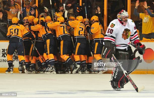 Kevin Fiala of the Nashville Predators is swarmed by teammates after scoring the game winning overtime goal against goalie Corey Crawford of the...
