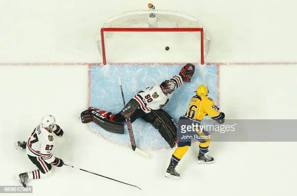 Kevin Fiala of the Nashville Predators scores the overtime game winning goal against Corey Crawford and Johnny Oduya of the Chicago Blackhawks in...
