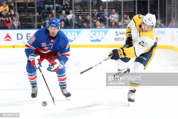 Kevin Fiala of the Nashville Predators shoots the puck against Michael Grabner of the New York Rangers at Madison Square Garden on October 21 2017 in...