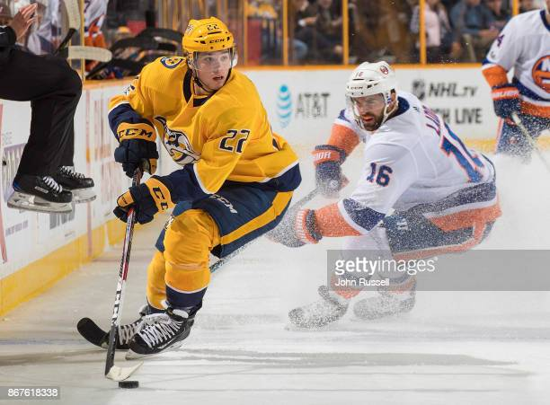Kevin Fiala of the Nashville Predators skates against Andrew Ladd of the New York Islanders during an NHL game at Bridgestone Arena on October 28...