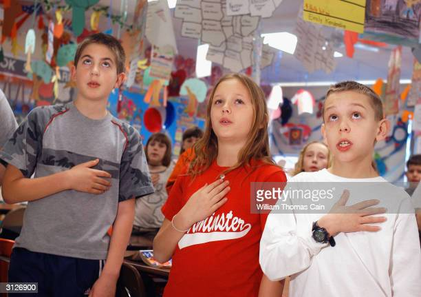 Kevin Flynn Brooke Zumwalt and Joseph Miller fourth grade students at Longstreth Elementary School pledge allegiance to the flag March 24 2004 in...