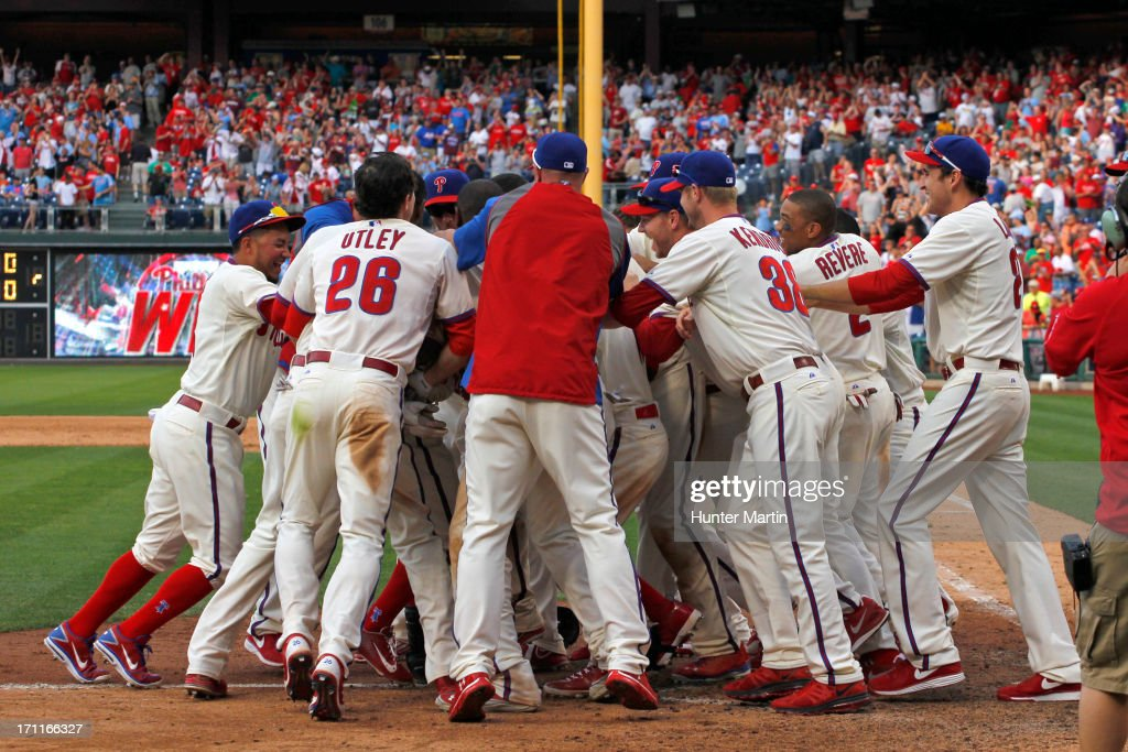 Kevin Frandsen #28 of the Philadelphia Phillies is mobbed by teammates after hitting a game-winning walk-off home run in the ninth inning during a game against the New York Mets at Citizens Bank Park on June 22, 2013 in Philadelphia, Pennsylvania. The Phillies won 8-7.